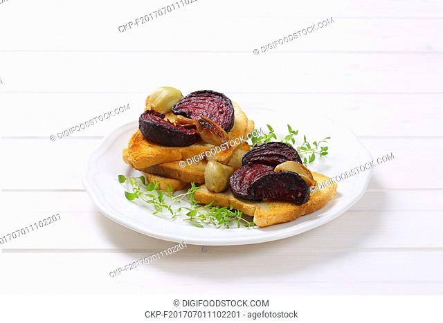 plate of toast with baked beetroot, garlic and thyme on white wooden background