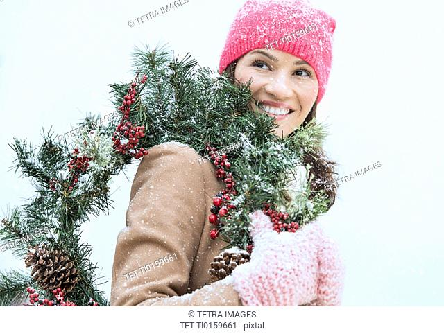 Portrait of woman in winter clothes carrying wreath