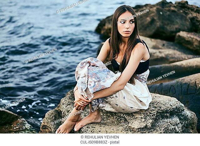 Young woman sitting on coastal rock looking over her shoulder, Odessa, Ukraine