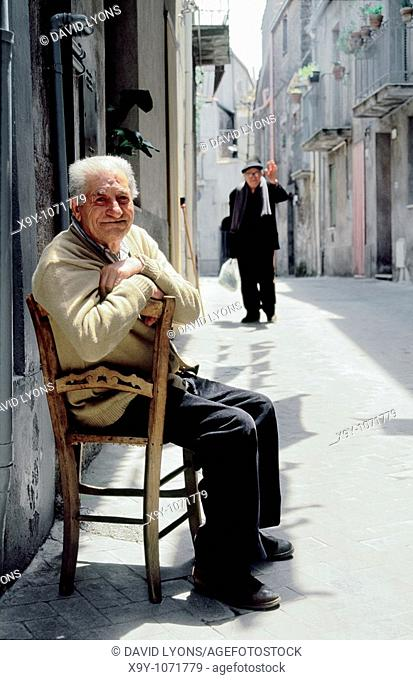 Old elderly local people men in street of hill town of Randazzo, central Sicily, Italy
