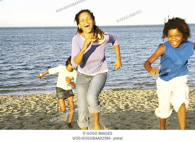 Young African woman racing with her sons on the beach