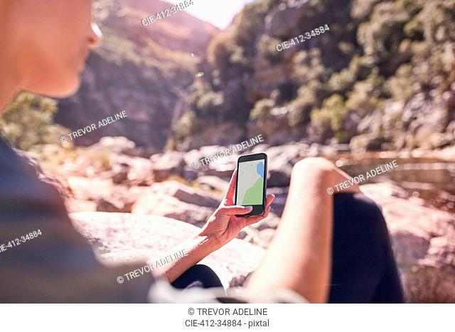 Young woman viewing digital map on smart phone at sunny stream