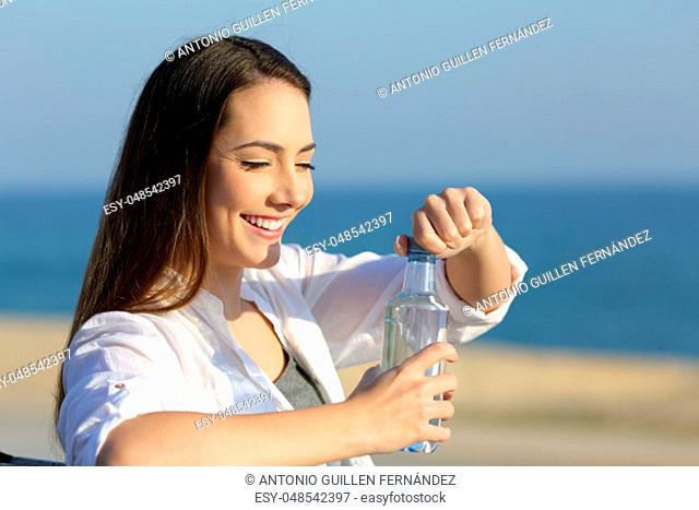 Portrait of a happy girl opeining a water bottle outdoors on the beach