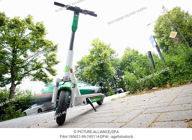 21 June 2019, Hamburg: An electric pedal scooter for rent stands on a parking lot at the roadside. Just under a week after the approval of the electric pedal...