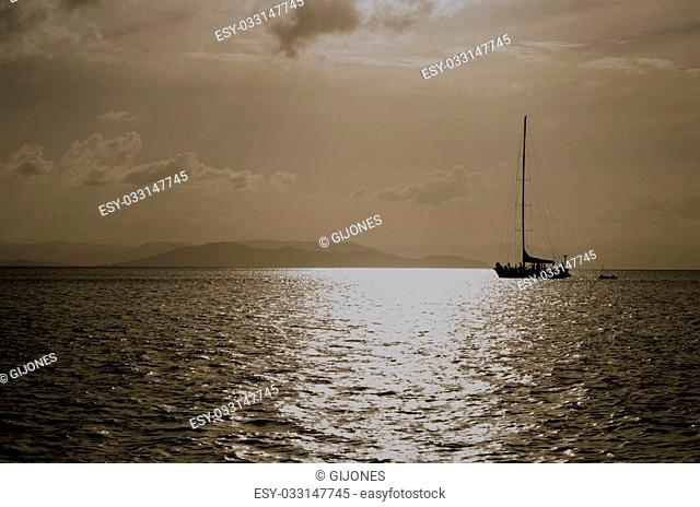 Large yacht with travelers on deck silhoutted against a setting sun in the Pacific