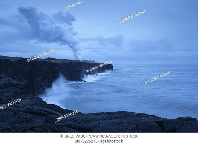 Coastline and steam plume from lava entering the ocean viewed from Holei Sea Arch overlook, Hawaii Volcanoes National Park, Island of Hawaii