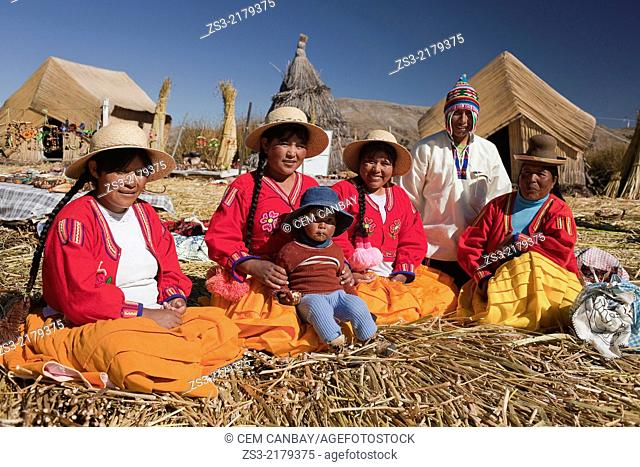 Aymara indigenous family posing with traditonal clothes, Uros Islands, Lake Titicaca, Puno Region, Peru, South America