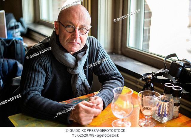 Rotterdam, Netherlands. Balding, middle aged man finishing his two glases of special beer