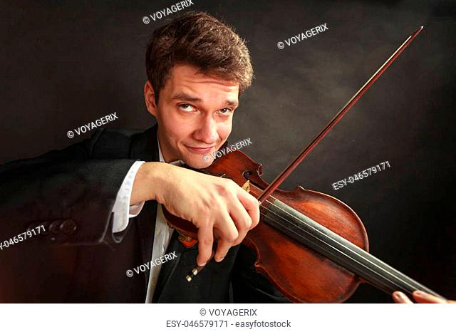 Music passion, hobby concept. Man playing violin showing funny emotions and face expressions. Studio shot on dark background