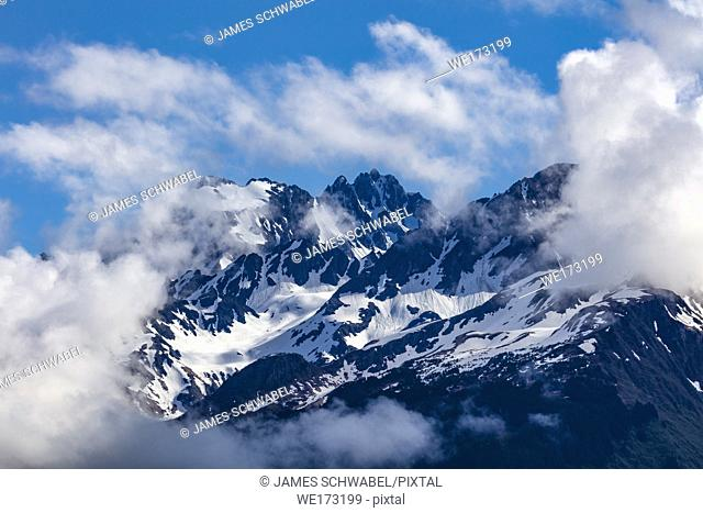 Snow capped rugged rocky mountains in clouds on the Kenai Peninsula of Alaska