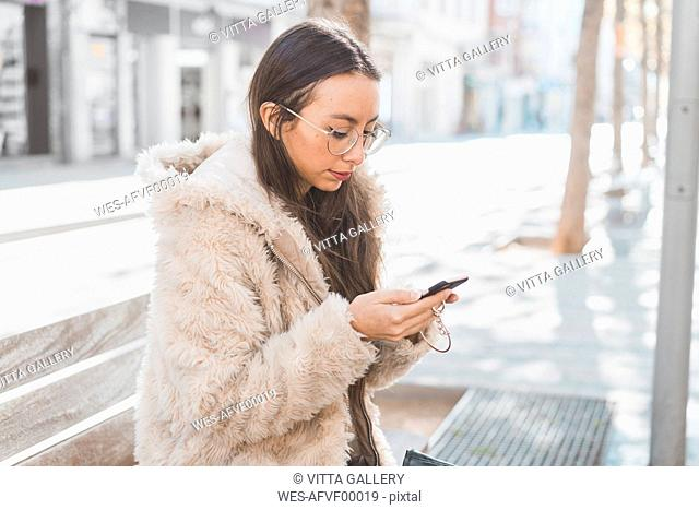 Stylish young woman in the city using cell phone