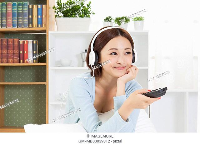 Young woman wearing headphone and looking away with smile