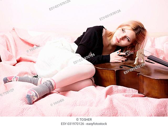 Young girl lying on a pink blanket with a cello