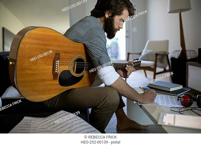 Man with guitar writing music in living room