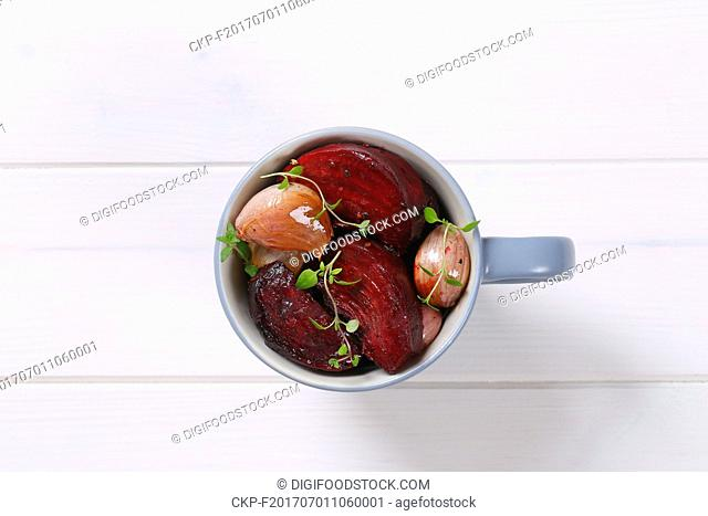 cup of baked beetroot with garlic and thyme on white wooden background