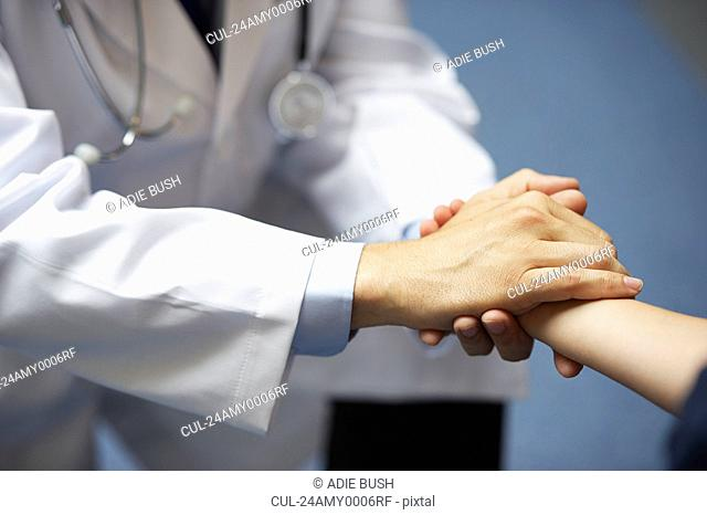Doctor holding young boy's hand