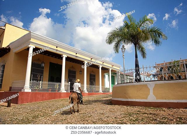 Old man riding on a donkey with the Iglesia de Santisima Trinidad Church at the background in town center, Plaza Mayor, Trinidad, Sancti Spiritu Province, Cuba