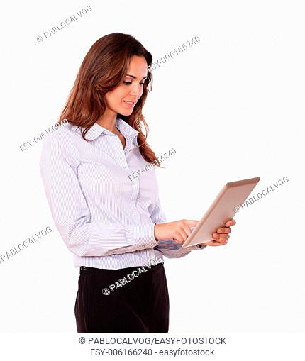 Portrait of a charming young woman working on tablet pc while standing on isolated background