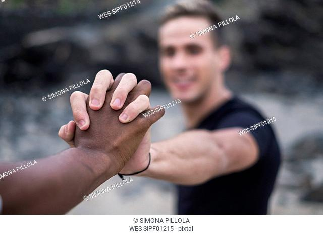 Close-up of young couple hand in hand