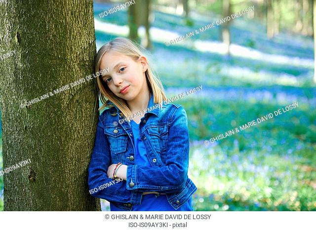Portrait of girl leaning against tree in bluebell forest, Hallerbos, Brussels, Belgium