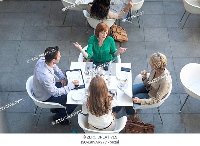 High angle view of businessmen and businesswomen having lunch meeting on hotel terrace
