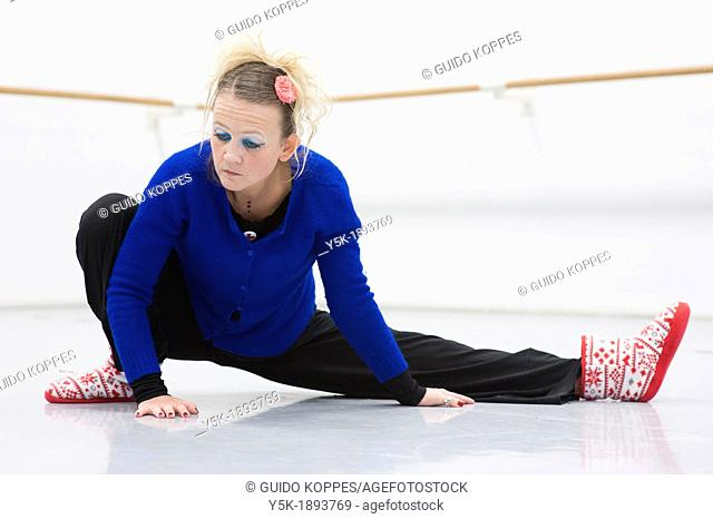 Tilburg, Netherlands. A professional dancer and choreographer of modern dance busy stretching and straightening her muscles before a rehearsal of improvised