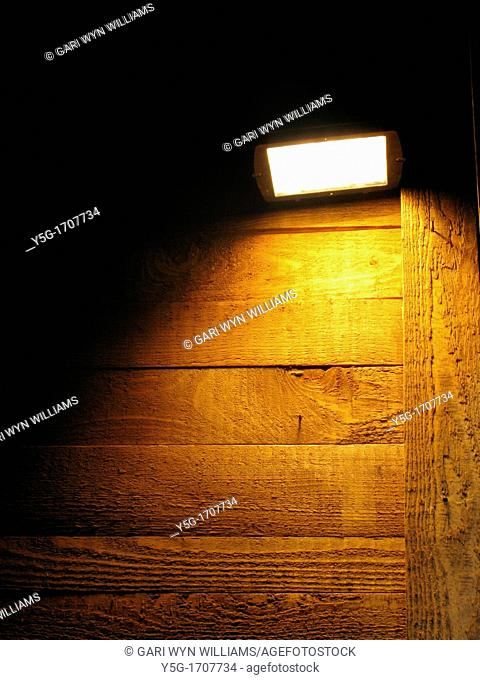 one bright light and high wooden wall at night