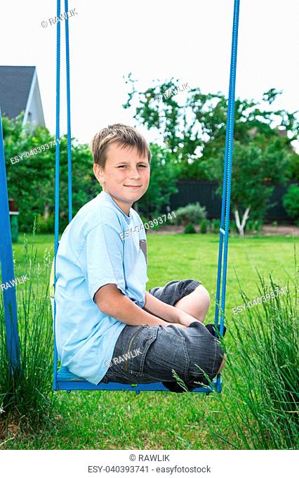 teenager sitting on a swing in the garden