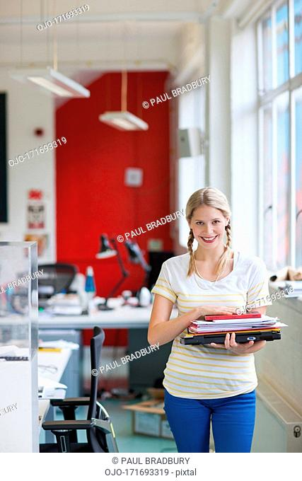 Smiling woman carrying laptop and paperwork in office