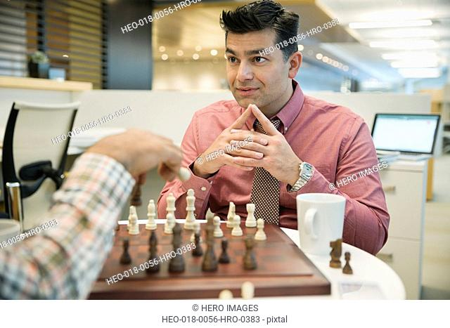 Businessman playing chess with coworker in office