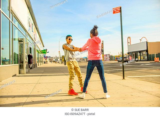 Teenage girl and boy spinning each other around on sidewalk, Brooklyn, USA