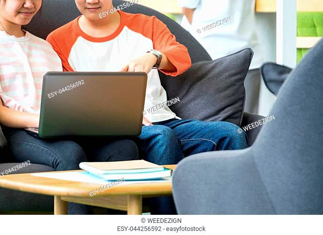 Two of asian teenage students studying together at sofa in library,Education concept