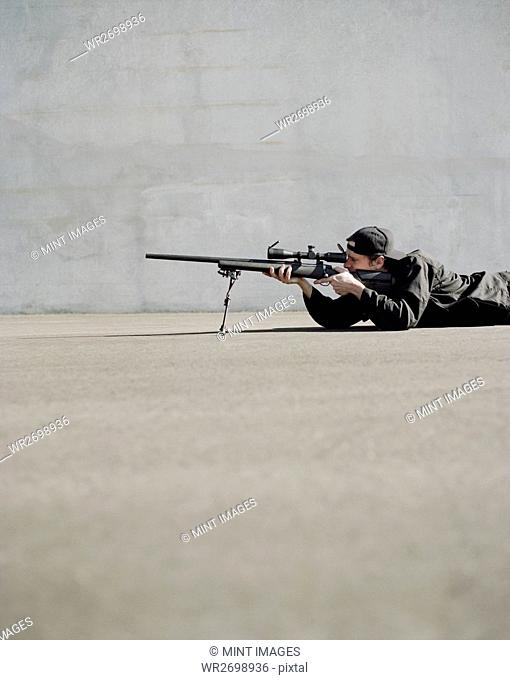 Man aiming high powered rifle, in sniper position