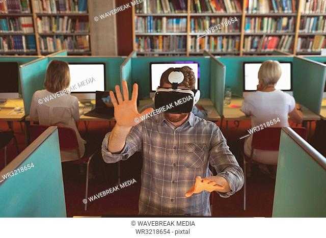 Male executive using virtual reality headset at desk