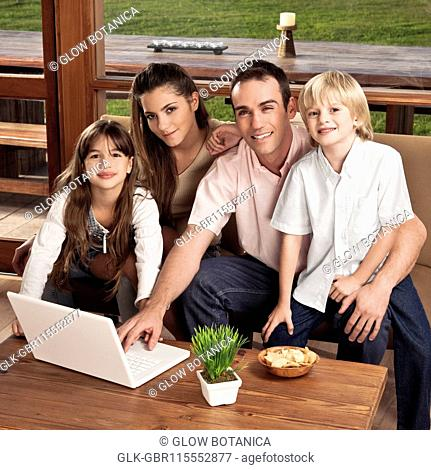 Portrait of a family with a laptop at home