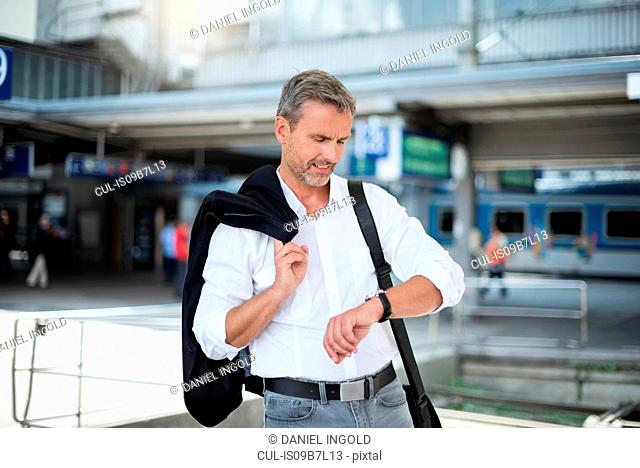Mature businessman looking at wristwatch in train station