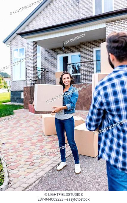 young beautiful couple with boxes moving into new house