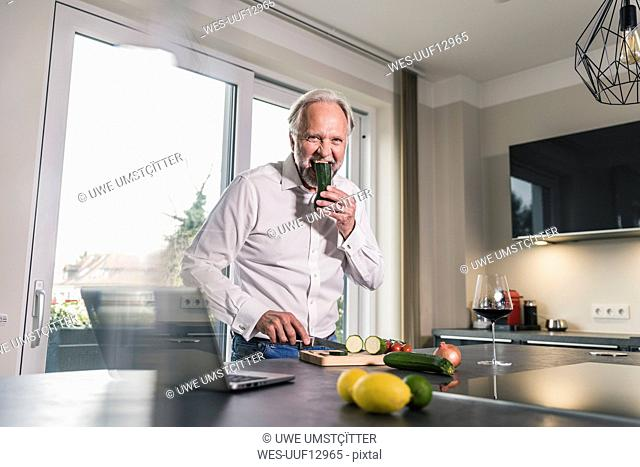 Funny mature man eating raw cougette in the kitchen