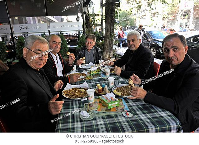 men enjoying ''lahmacun'', thin piece of dough topped with minced meat, served with ''than'' or ''Ayran'', kind of yogurt, at the Mer Taghe restaurant, Yerevan