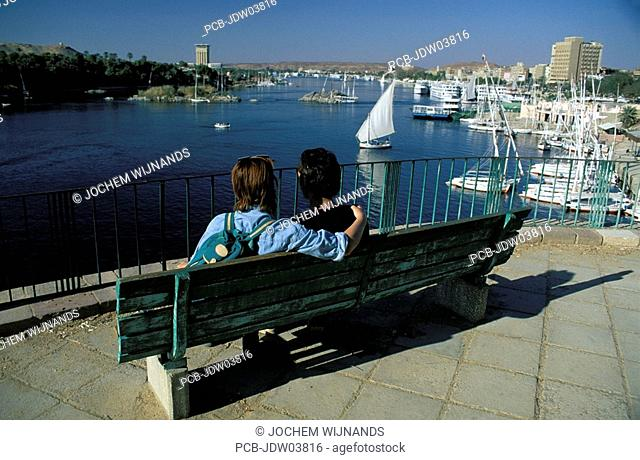 Aswan, a couple watching the felucca sailboats on the Nile river