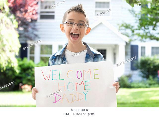 Caucasian boy holding Welcome Home Daddy sign