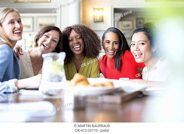 Portrait laughing women friends dining at restaurant table