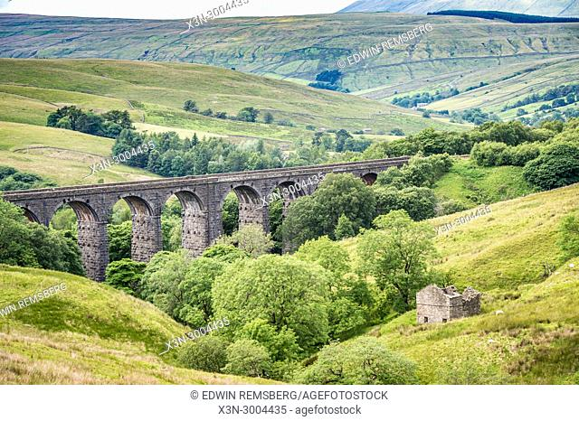 Extensive stone bridge allows for trains to cross over rolling hills of the Dales, Yorkshire Dales, UK