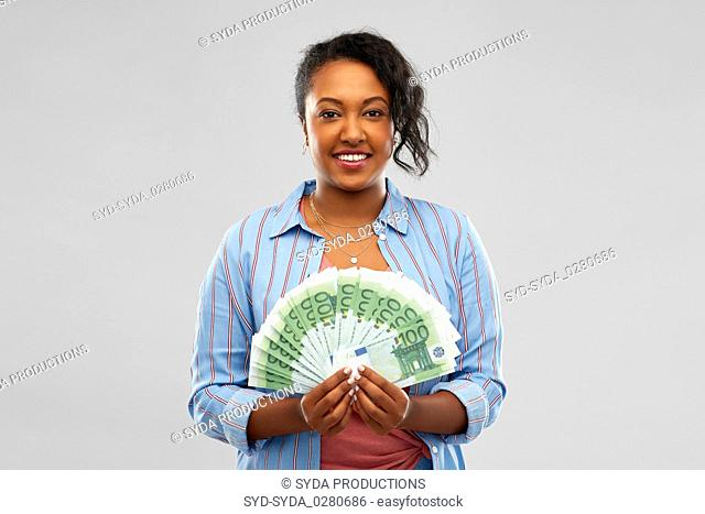 happy african american woman holding euro money