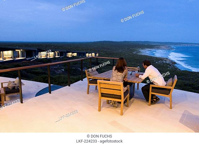 A couple sitting on the terrace of Southern Ocean Lodge in the evening, Kangaroo Island, South Australia, Australia