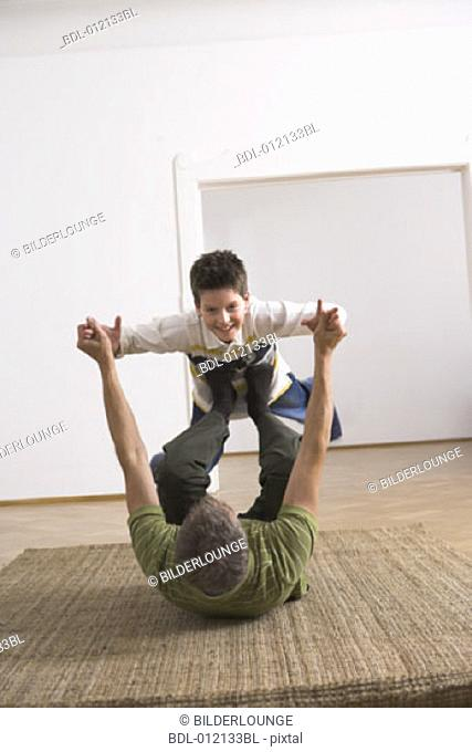 portrait of young boy being lifted in the air by his father