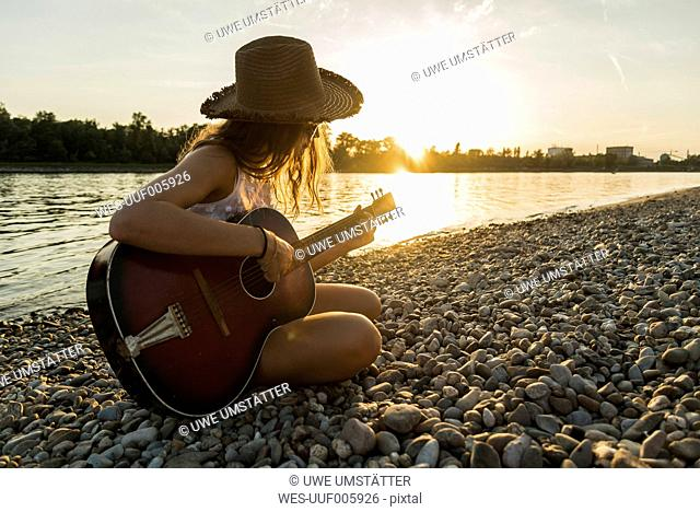Young woman playing guitar at the riverside at sunset