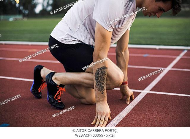 Runner on tartan track in starting position
