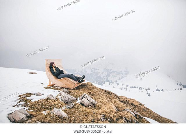 Austria, Kitzbuehel, Kitzbuehel Horn, young woman relaxing on deckchair in winter looking at view