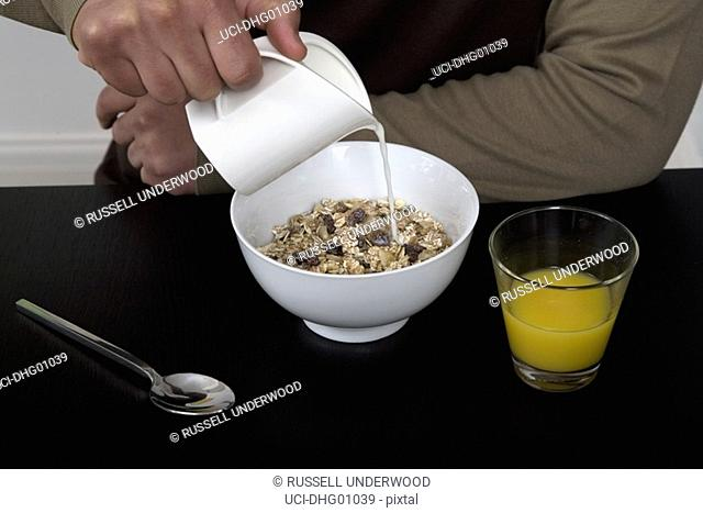 Close up of young man pouring milk on cereal